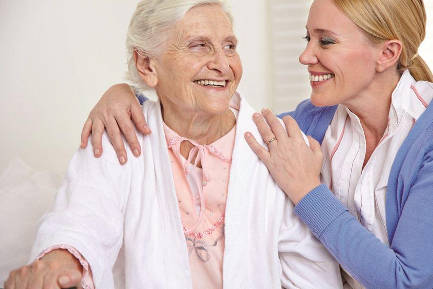 Lächelnde Frau umarmt eine glückliche Seniorin im Seniorenheim